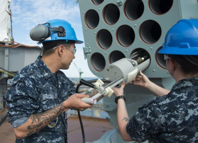 Fire Controlman 2nd Class Shelby Edson and Fire Controlman 3rd Class Lawrence Batcheller insert a Load-Out Test Adapter into a Rolling Airframe Missile (RAM) launching system