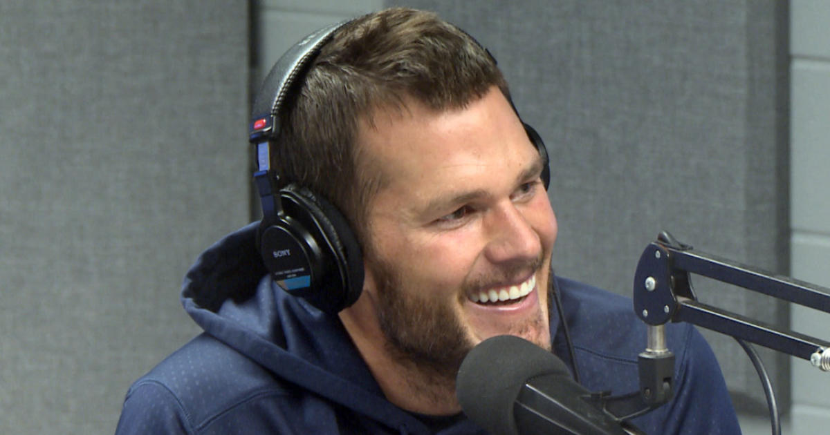Tom Brady wears headphones and talks into a radio mic