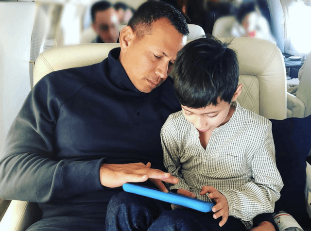 Jennifer Lopez's son playing with a device on Alex Rodriguez's lap.