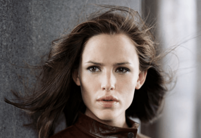 Jennifer Garner stands in front of a gray wall.