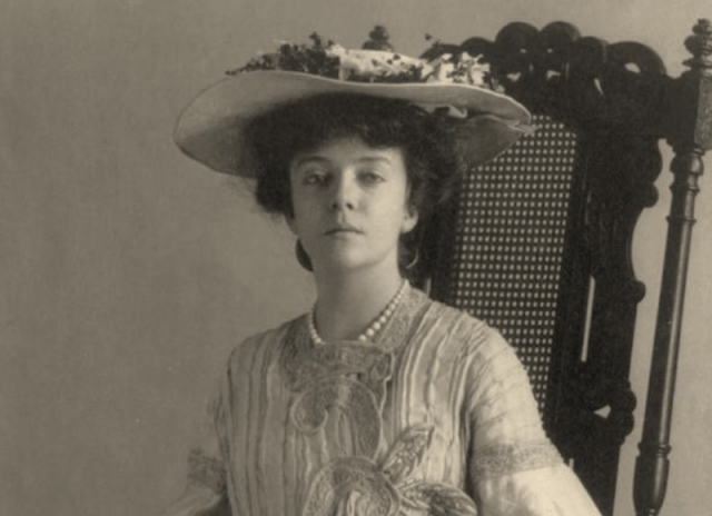 Alice Roosevelt sitting in a chair while wearing a hat.
