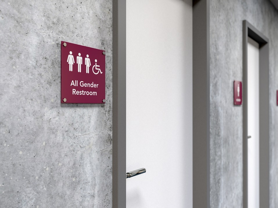An all gender rest room sign next to a bathroom door