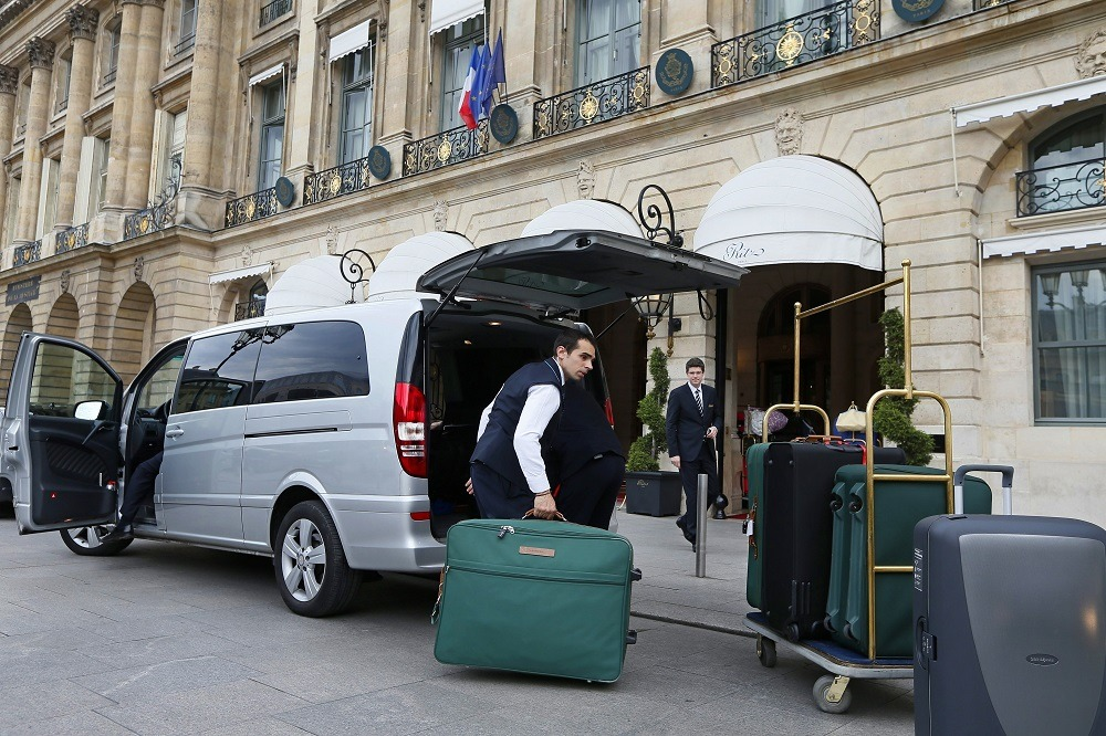 An employee from the Ritz luxury hotel loads luggage in a van in Paris