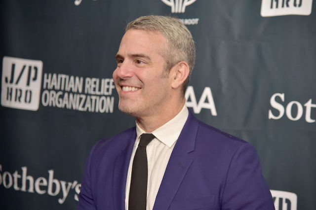 Andy Cohen wearing a blue suit and tie as he smiles on a red carpet.