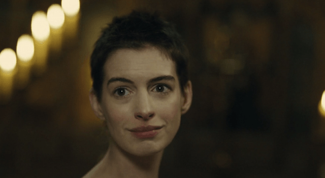 Anne Hathaway looking to the side and smiling in 'Les Miserables'.