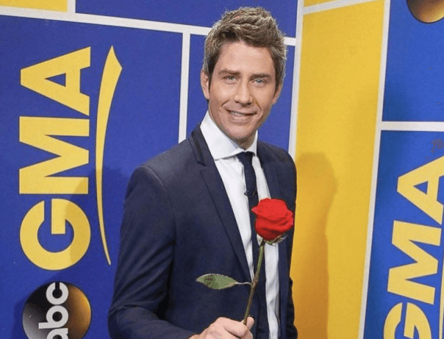 Arie holds up a red rose.
