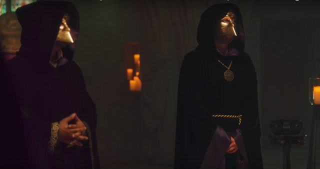 Two men dressed in cloaks and face masks.