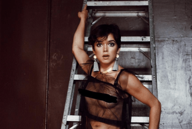 Bekah Martinez posing in front of a ladder.