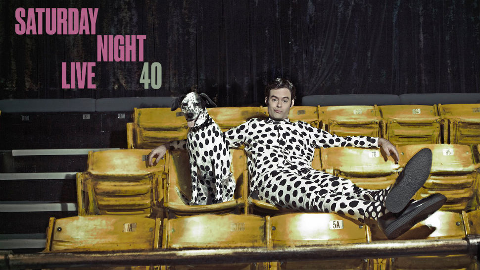 Bill Hader posing on the audience chairs in a promotional image for the Saturday Night Live 40th Anniversary Special