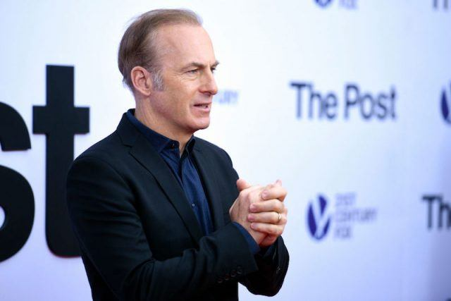 Bob Odenkirk posing on a red carpet while holding his hands.