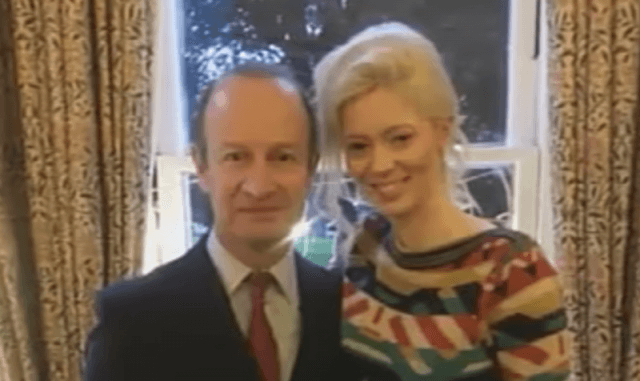 Henry Bolton poses for a photo with Jo Marney in front of a window.