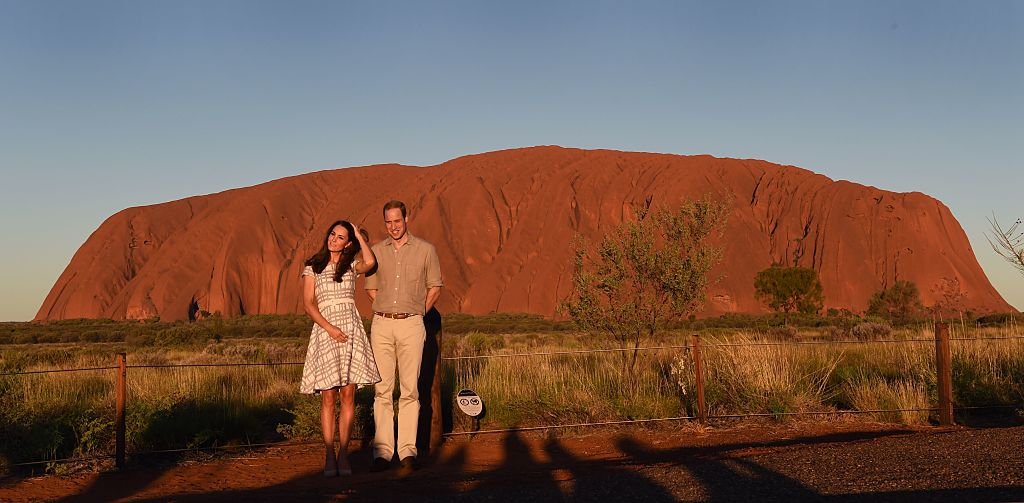 Prince William (R) and his wife Catherine, the Duchess of Cambridge, stand in front of Uluru