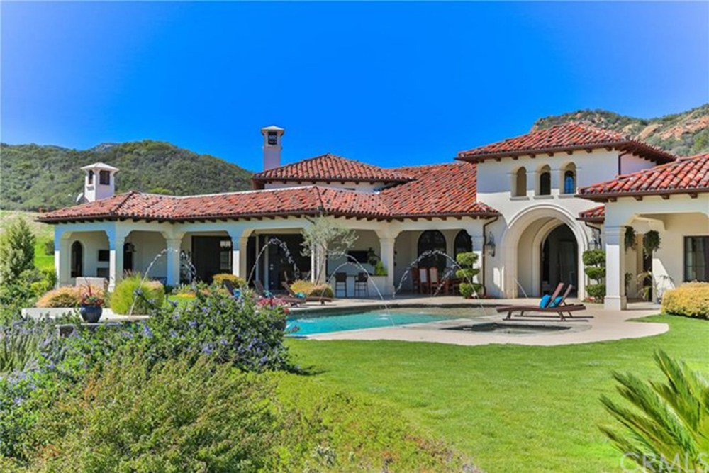 Back of Spanish style home with pool