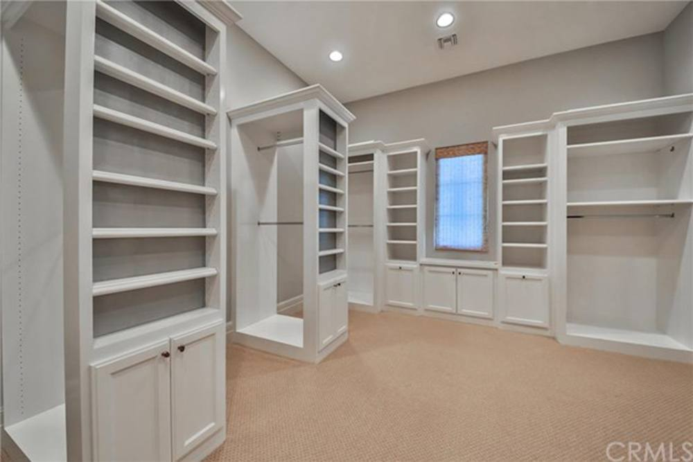A large, white walk i closet with shelves and hanging space