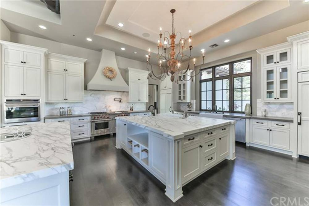 Britney Spears' White kitchen with marble counters and large island.