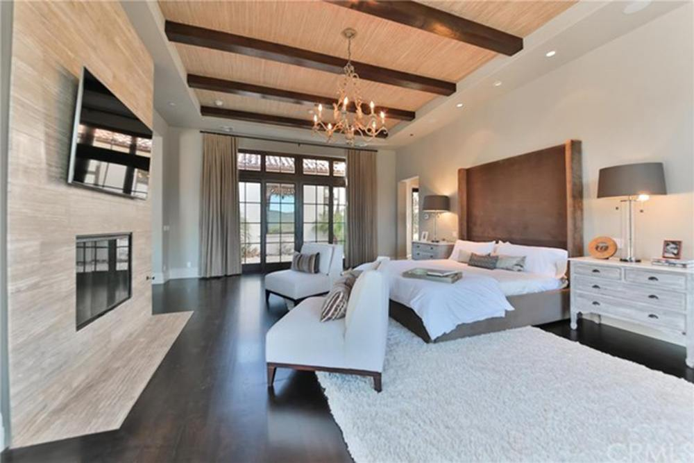 Giant master bedroom with beamed ceilings, chandelier, and fireplace