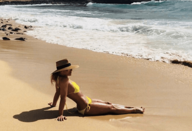 Britney Spears laying on a sandy beach.