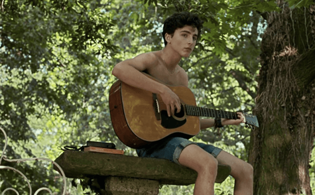 A young boy plays a guitar while sitting at a bench.