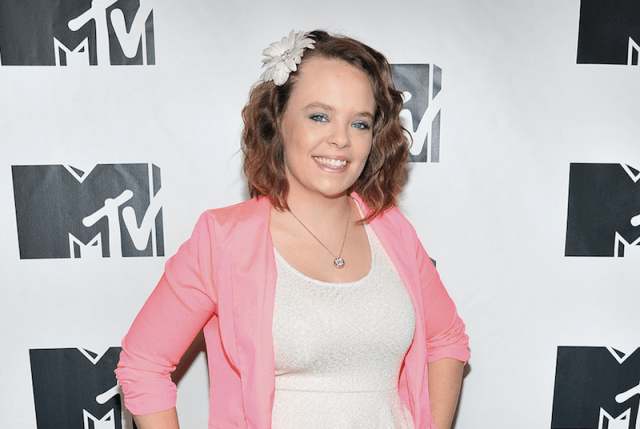 Catelynn smiling while wearing a white dress and pink jacket.