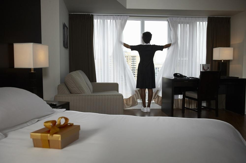 A hotel maid opening the curtains in a room