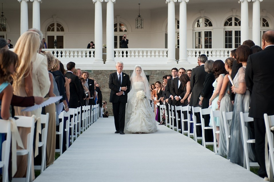 former U.S. President Bill Clinton (L) walks Chelsea Clinton down the aisle during her wedding