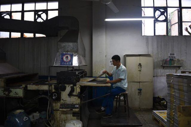A factory worker working with a tool on a desk.