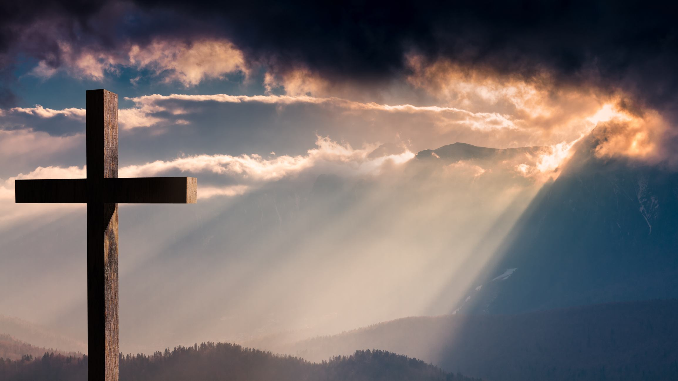 Jesus Christ wooden cross on a dramatic, colorful sunset