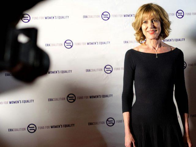 Christine Lahti posing for the paparazzi on a red carpet.