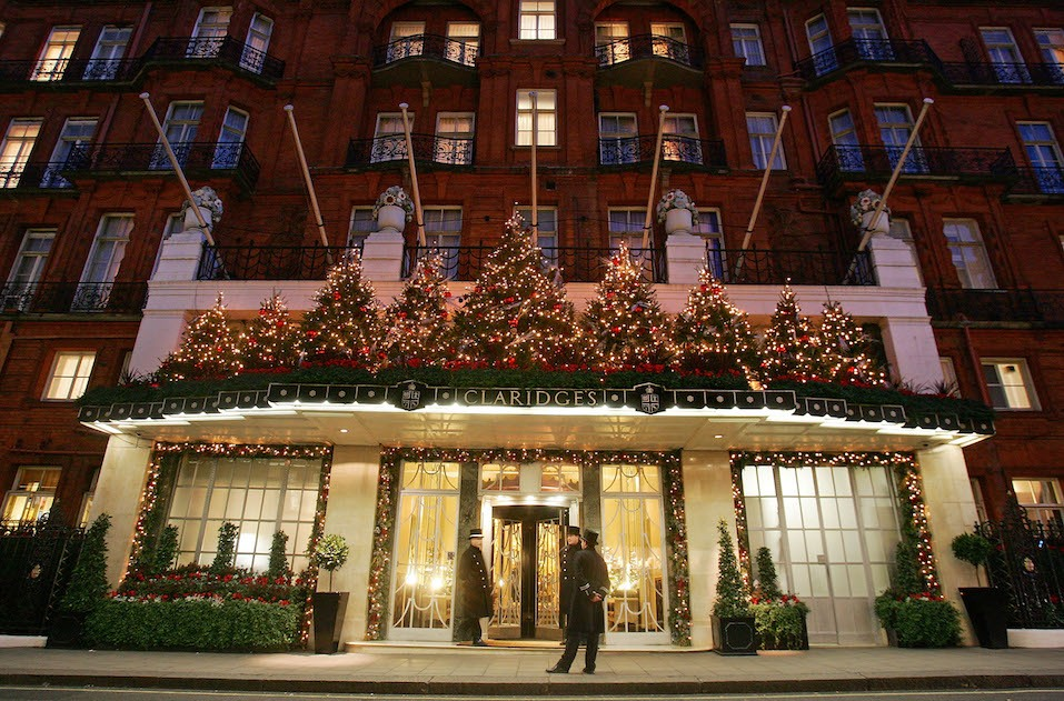 Doormen stand on duty in front of Claridge's Hotel which is lit up for Christmas