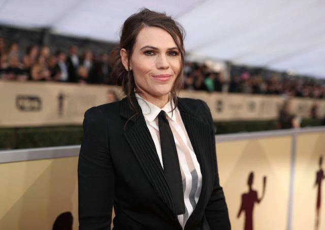 Clea DuVall smiling while wearing a tuxedo and tie.