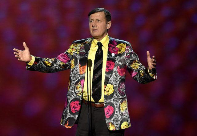 Craig Sager stands on stage in front of a microphone.