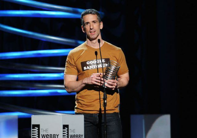 Dan Savage holds an award while standing in front of a microphone on stage.