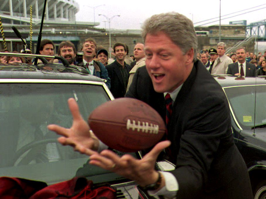 Democratic presidential candidate Bill Clinton catches a football