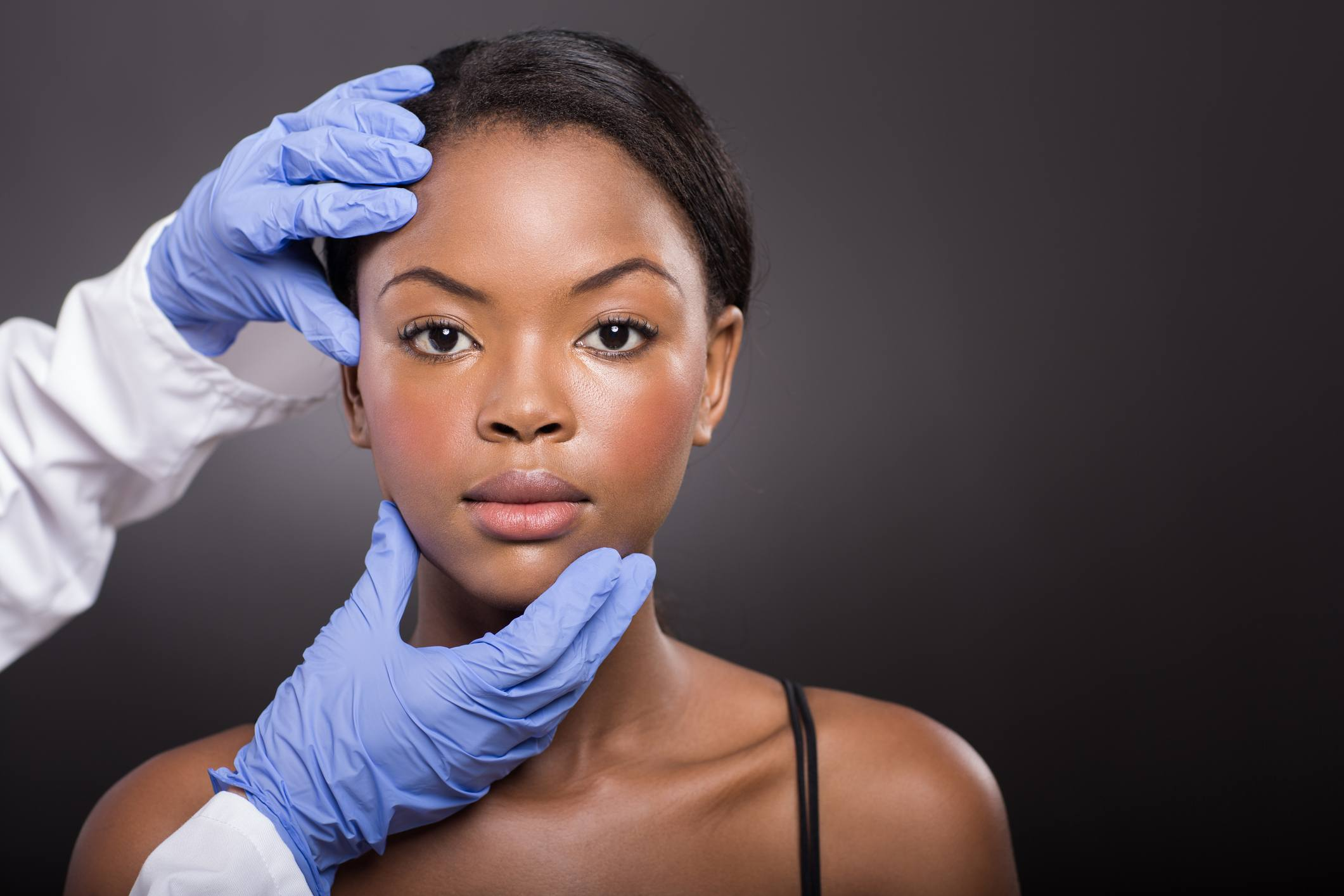 dermatologist checking african woman face skin