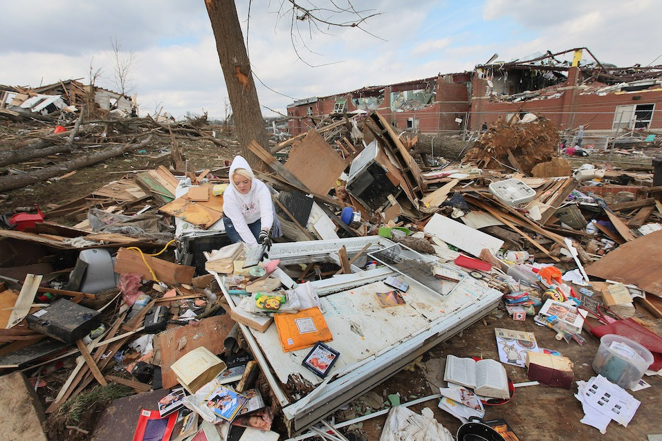 Lori Hall searches for items to salvage in the home of her aunt and uncle after it was destroyed by Friday's EF-4 tornado