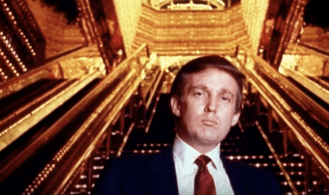 Donald Trump poses in front of a staircase.