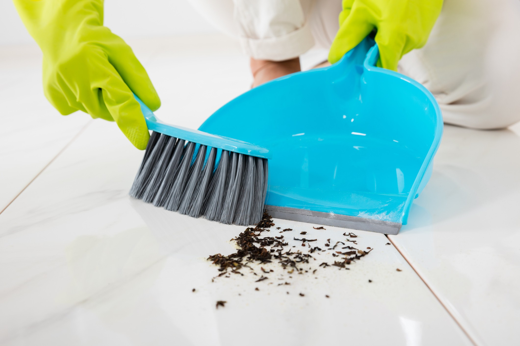 Person Sweeping Floor With Broom And Dustpan