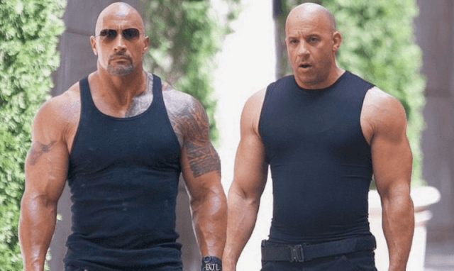 Dwayne Johnson and Vin Diesel stand together wearing black tank tops.