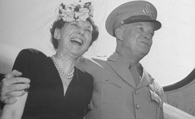 Mamie Eisenhower and Dwight D. Eisenhower smiling and posing in front of photographers.
