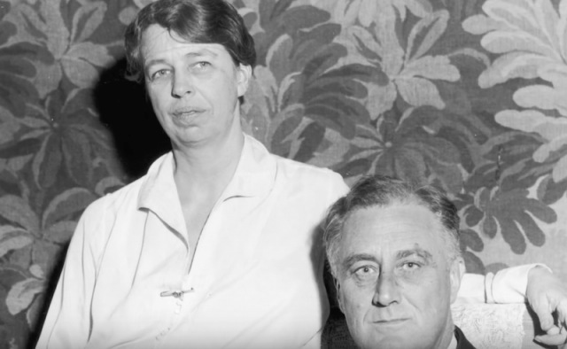 Eleanor stands with her arm around the chair that Franklin D. Roosevelt is sitting on.
