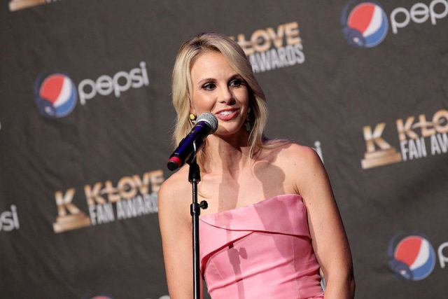 Elisabeth Hasselbeck standing behind a microphone while wearing a pink dress.