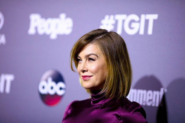 Ellen Pompeo smiling on a red carpet while wearing a purple dress.