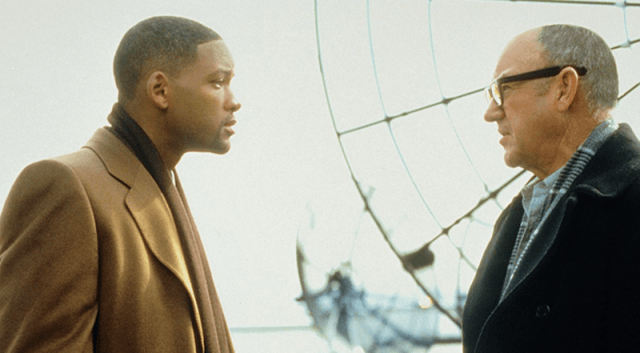 Will Smith and Gene Hackman talking in front of a large wheel in 'Enemy State of Mind'.