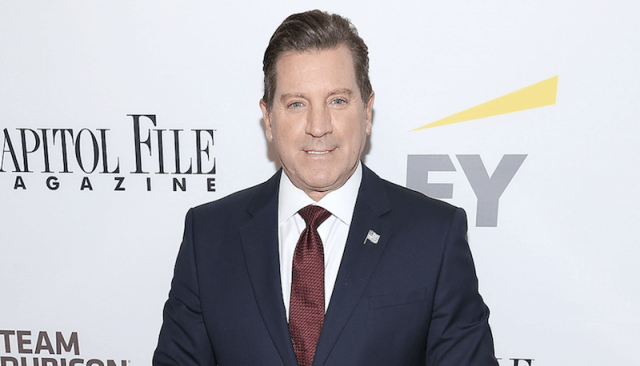 Eric Bolling posing on a red carpet in a black suit and red tie.