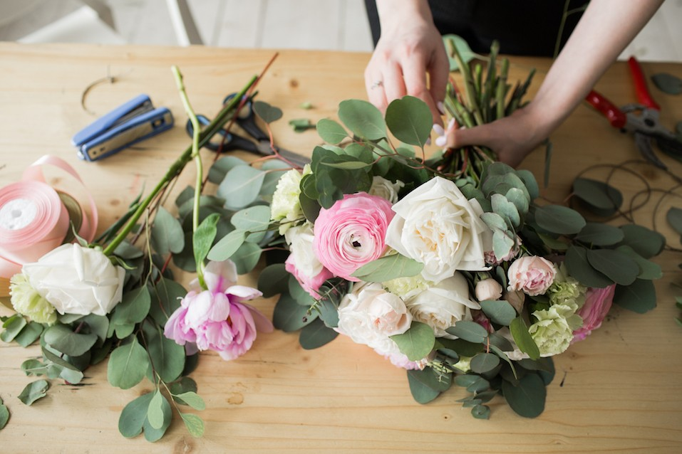Young woman making fashion modern bouquet of different flowers.