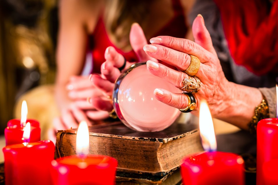 Female Fortuneteller sees in the future by looking into their crystal ball