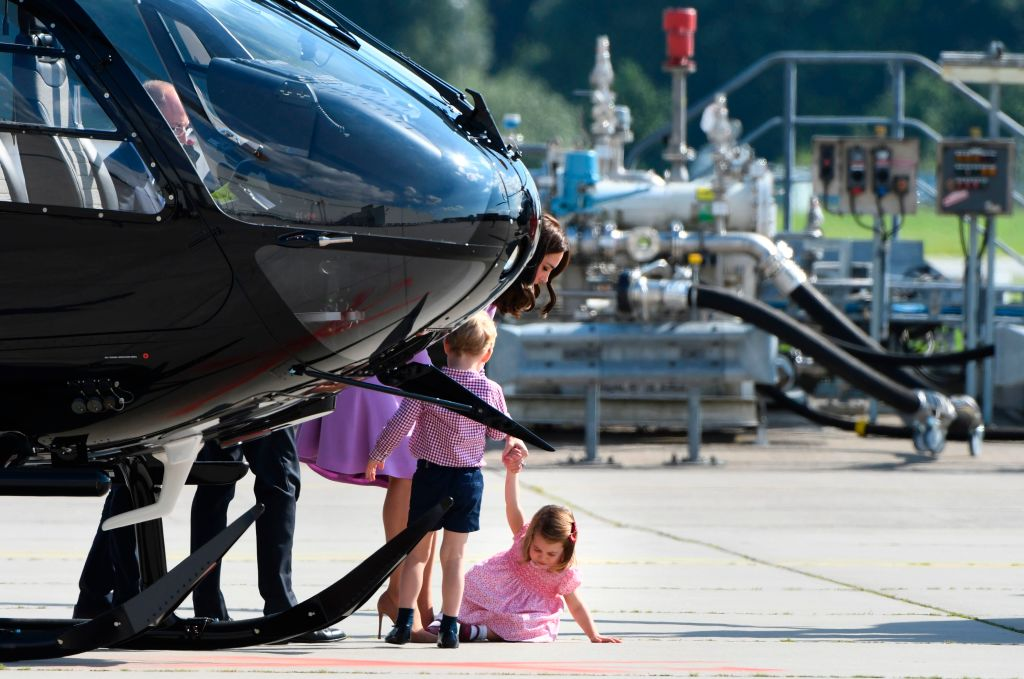 Britain's Princess Kate, the Duchess of Cambridge, attends to her children Prince George and Princess Charlotte as they visit an Airbus helicopter