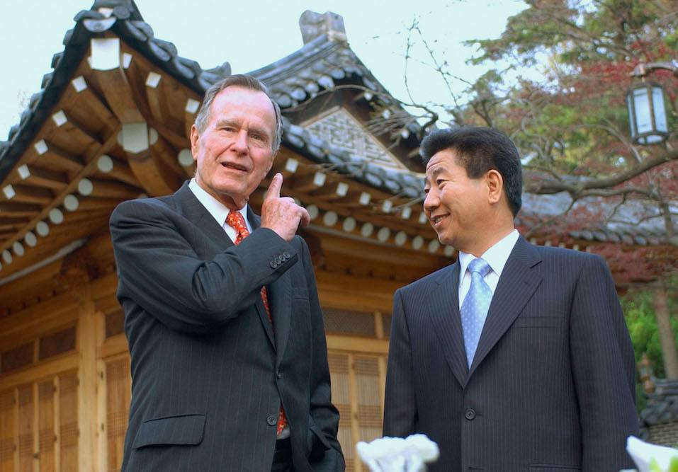 Former U.S. President George H. Bush talks with South Korean President Moo-Hyun