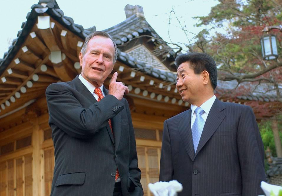Former U.S. President George H. Bush talks with South Korean President Moo-Hyun