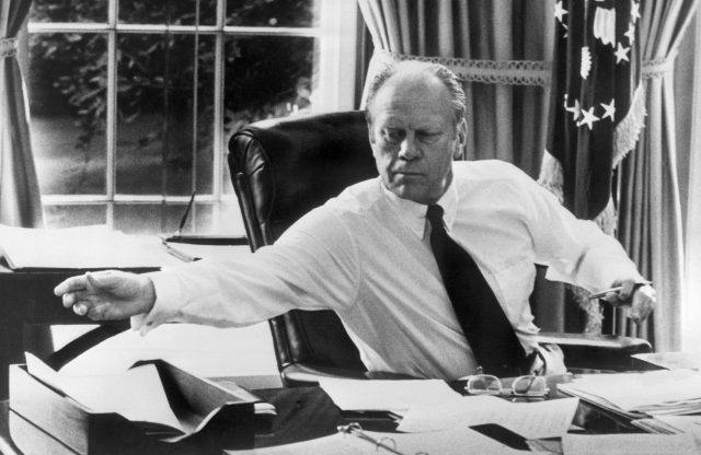 Gerald Ford reaching forward while sitting in his desk.